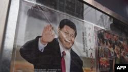 在北京街道旁玻璃窗宣传栏里展示的中国国家主席习近平的宣传画(2018年2月28日)。