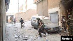 Forces loyal to President Bashar al-Assad are seen at Suleiman al-Halabi neighborhood in Aleppo, Syria, September 20, 2012.