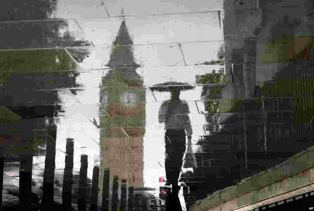 (8月4日)在烟雨蒙蒙中,一位行人的孤独身影倒映在伦敦大本钟边。