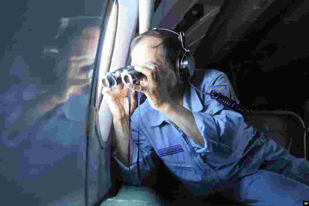 A Vietnamese Air Force colonel uses binoculars on board a flying aircraft during a mission to search for the missing Malaysia Airlines flight MH370 in the Gulf of Thailand, March 13, 2014.