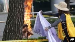 一名韩国男子(左)在日本驻首尔大使馆外自焚,抗议二战期间日本慰安妇暴行。一名妇女试图扑灭他身上的火。 (2015年8月12日)