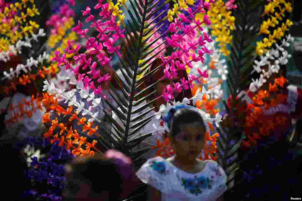 Girls dressed in traditional costumes take part in the festivity of the Holy Cross to ask for a good rainy season in Panchimalco, El Salvador.