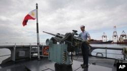 FILE - A member of the Philippine Navy demonstrates one of the guns on board the BRP Gregorio Del Pilar (PF15) warship at Manila's pier, amid tensions with China over the disputed Spratly Islands in the South China Sea, Dec. 17, 2014.