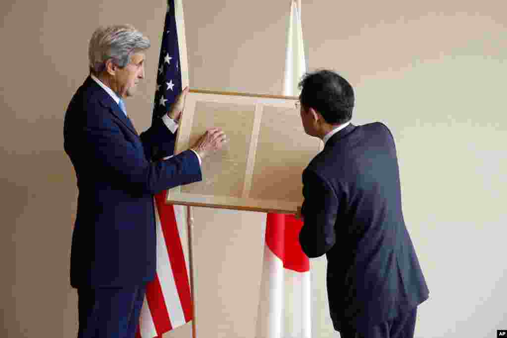 U.S. Secretary of State John Kerry, left, points out to Japan's Foreign Minister Fumio Kishida a passage about friendship in a replica of a letter on a small diplomatic matter from former U.S. President Abraham Lincoln to the Tycoon of Japan in 1861, before their bilateral meeting in Hiroshima, Japan, April 11, 2016.