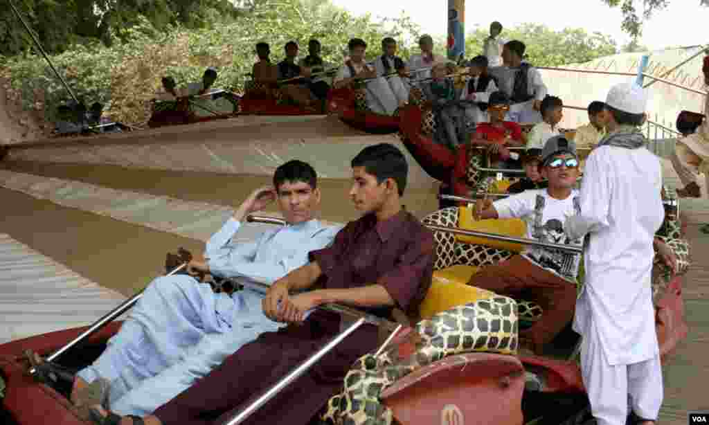 کراچی کے چڑیا گھر میں جھولوں کا لطف اٹھاتے دو دوست اور دیگر نوجوان