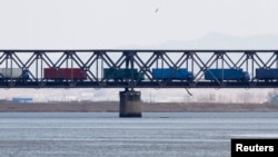 FILE - Trucks drive on the Friendship Bridge over the Yalu River which connects North Korea's Sinuiju to China's Dandong, April 11, 2013.