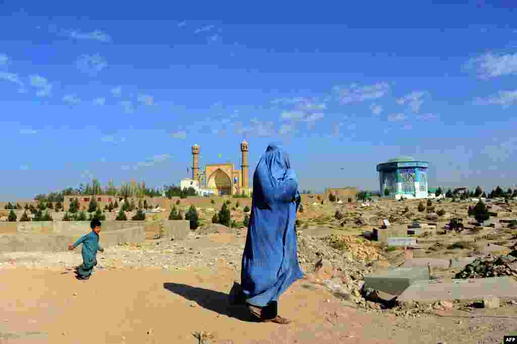 A burqa-clad Afghan woman walks near a cemetery in Herat province, Afghanistan.