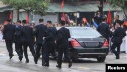 Các vệ sĩ chạy theo chiếc limousine chở lãnh đạo Triều Tiên Kim Jong Un từ ga Đồng Đăng đi Hà Nội ngày 26/2/2019.