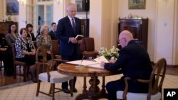 Malcolm Turnbull, center, is sworn in by Australia's Governor-General Sir Peter Cosgrove, right, as prime minister at Government House in Canberra, Tuesday, Sept. 15, 2015.