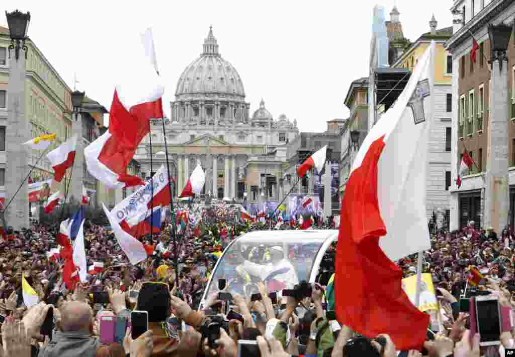 Pope Francis greets the faithful as he is driven through the crowd along Via della Conciliazione while celebrating the ceremony for the canonizations of Pope John XXIII and Pope John Paul II in St. Peter's Square, at the Vatican, April 27, 2014.