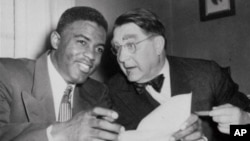 Atlet bisbol AS Jackie Robinson dan presiden tim Brooklyn Dodgers Branch Rickey tahun 1950.
