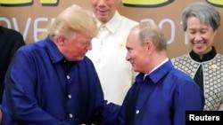 Los presidentes Donald Trump de EE.UU. (izquierda) y Vladimir Putin de Rusia se estrecharon la mano durante la cena en la cumbre de APEC en Vietnam, el viernes, 10 de noviembre de 2017.