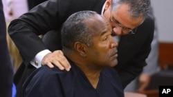 O.J. Simpson escucha a su abogado, Ozzie Fumo, durante la audiencia ante el consejo de libertad condicional en Nevada.
