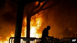FILE - In this Feb. 1, 2017, photo, a fire set by demonstrators protesting a scheduled speaking appearance by Breitbart News editor Milo Yiannopoulos burns on Sproul Plaza on the University of California, Berkeley campus.