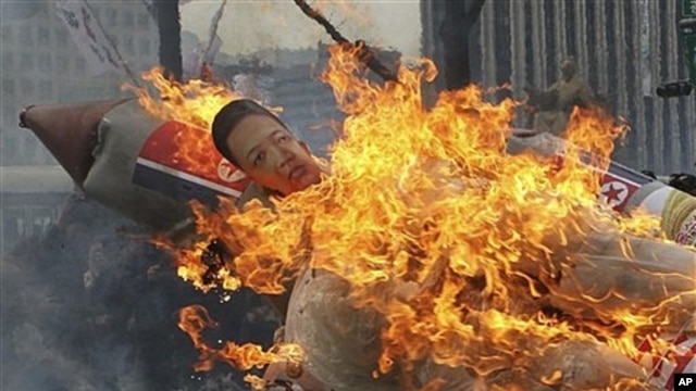 Effigy of North Korea's Kim Jong Un on burning mock missile at Seoul protest, South Korea, April 13, 2012.