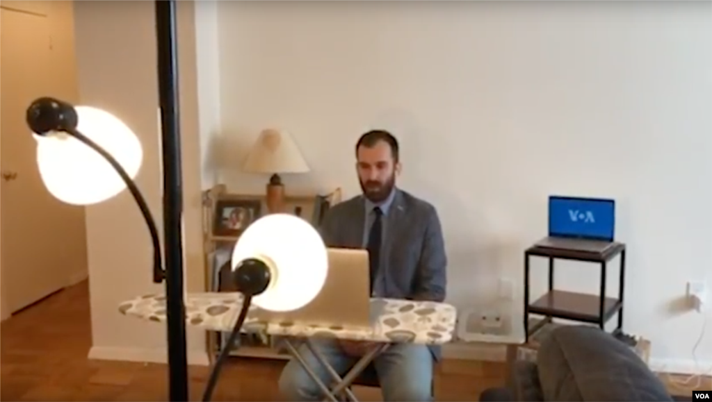 Transforming his living room into a self-isolation studio for live TV interviews to affiliate stations in Bosnia, VOA's Bosnian service journalist, Dino Jahic, uses his ironing board to double as an anchor desk to set up an in-home camera on his laptop for live broadcasts.