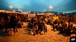 People sit on the ground at a refugee camp in the southern Macedonian town of Gevgelija, Sept. 8, 2015.