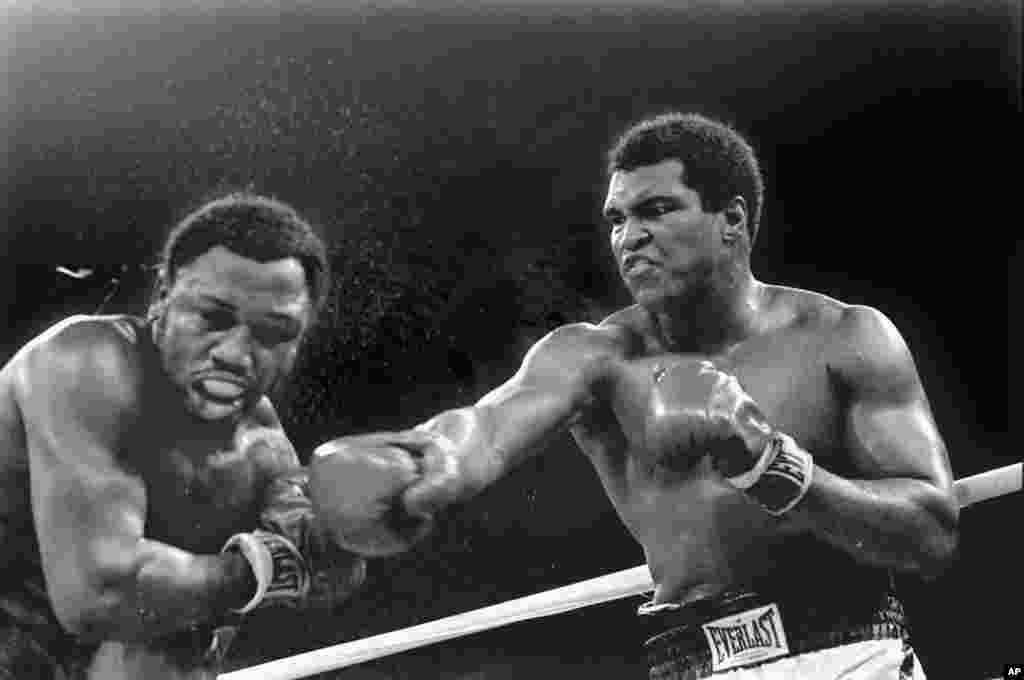 រូបឯកសារ៖ ទឹកបែកខ្ចាយចេញពីកីឡាករ Joe Frazier ខណៈដែល Muhammad Ali ជើងឯកទម្ងន់ធ្ងន់ប្រើកណ្តាប់ដៃស្តាំវាយ នៅជុំទី៩នៃការប្រកួតដណ្តើមខ្សែក្រវ៉ាត់នៅក្នុងទីក្រុងម៉ានីល ប្រទេសហ្វីលីពីន។