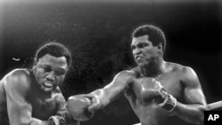 FILE - Spray flies from the head of challenger Joe Frazier as heavyweight champion Muhammad Ali connects with a right in the ninth round of their title fight in Manila, Philippines, Oct. 1, 1974.