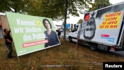 FILE - Workers remove election campaign posters showing candidates for the Green Party and Free Democratic Party (FDP) a day after the German general elections, in Cologne, Germany, Sept. 27, 2021.