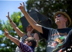 Mourners hold up peace signs during Gregg Allman's burial at Rose Hill Cemetery, June 3, 2017, in Macon, Ga. Family, friends and fans gathered to say goodbye to music legend Gregg Allman, who died Memorial Day weekend at the age of 69.