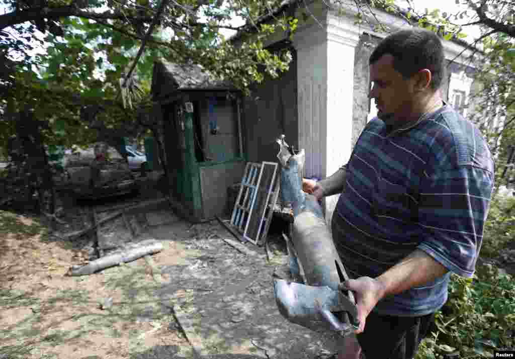 A man holds the remains of a rocket which he said was fired by Ukrainian army. Donetsk, Aug. 12, 2014.