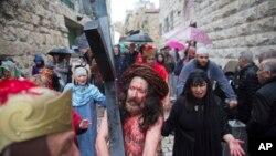 Un actor vestido como Jesucristo lleva una cruz al recrear su camino hacia la crucifixión en la Vía Dolorosa, en la Ciudad Vieja de Jerusalén, el viernes, 30 de marzo, de 2018, durante una tradición del Viernes Santo.