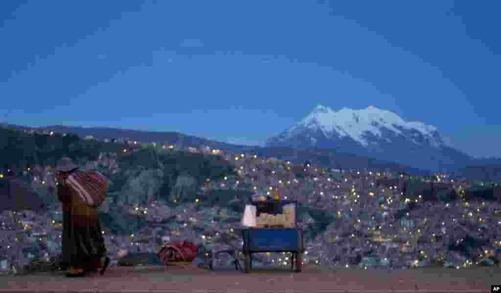 ស្រ្តីម្នាក់ដើរតាមដងផ្លូវ Pereferica Avenue កាត់តូបលក់ពោតលីងមូយ ហៅថា«pipocas» ដោយមានភ្នំ Illimani Mountain នៅខាងក្រោយអំឡុងពេលព្រះអាទិត្យលិចនៅក្នុងទីក្រុង La Paz ប្រទេសបូលីវី។