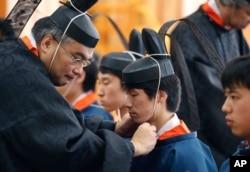 지난 1월 코쿠카쿠인 대학에서 성인의 날은 맞아 교수들이 20살이 된 학생들에게 의식용 모자를 씌우고 있다.