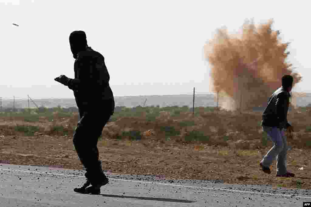 April 1: Rebels run from explosions and an incoming mortar during a barrage fired by troops loyal to Muammar Gaddafi outside Brega in eastern Libya. (Reuters)