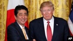 Presiden AS Donald Trump (kanan) dan PM Jepang Shinzo Abe berjabat tangan usai mengadakan konferensi pers bersama di Gedung Putih, Jumat (10/2).