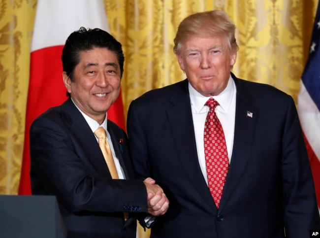 FILE - President Donald Trump, right, and Japanese Prime Minister Shinzo Abe shake hands following their joint news conference in the East Room of the White House in Washington, Feb. 10, 2017.