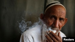 FILE - A man smokes a cigarette in a public place in the northern in the state of Uttar Pradesh, India, April 2014.