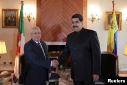 Venezuela's President Nicolas Maduro, right, shakes hands with Algeria's Senate President Abdelkader Bensalah during their meeting in Algiers, Algeria, Sept. 11, 2017.