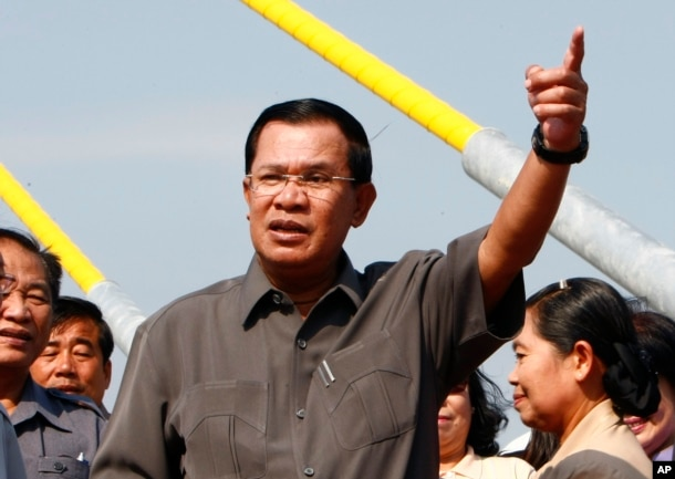 Cambodia's Prime Minister Hun Sen, center, gestures during a ceremony inaugurating the country's longest bridge in Neak Loeung, southeast of Phnom Penh, Cambodia, Wednesday, Jan. 14, 2015. Hun Sen, Cambodia's tough and wily prime minister, marks 30 years in power Wednesday, one of only a handful of political strongmen worldwide who have managed to cling to their posts for three decades. (AP Photo/Heng Sinith)