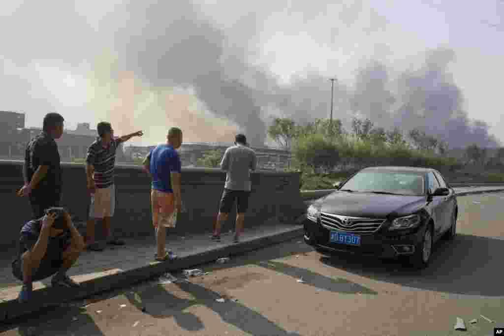 Residentes se juntam perto do lugar da explosão no porto de Tianjin, China,13 de Agosto, 2015.