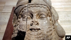 FILE - The head of a winged bull made out of limestone was restored and displayed at the Iraqi National Museum in Baghdad. Now much of that archaeological wealth is under the control of extremists from the Islamic State group, Sept. 15, 2014.