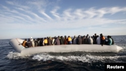 FILE - Migrants, who tried to flee to Europe, travel in a dinghy after they were stopped by Libyan coast guards and made to head to Tripoli, Sept. 29, 2015.