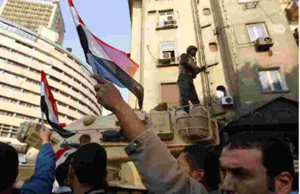 Los manifestantes alzan las banderas después de conocer la victoria.