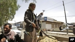 Armed Yemeni tribesmen stand guard in a street in Sanaa, Yemen, May 29, 2011