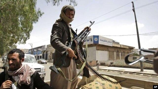 Armed Yemeni tribesmen stand guard in a street in Sanaa, Yemen, May 29, 2011