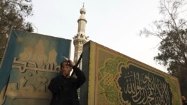 A man standing in front of Moqattam mosque takes a photo near the Muslim Brotherhood's national headquarters in Cairo's Moqattam district March 22, 2013.