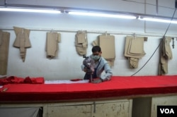A worker is busy cutting garments at an apparel factory. (A. Pasricha/VOA)