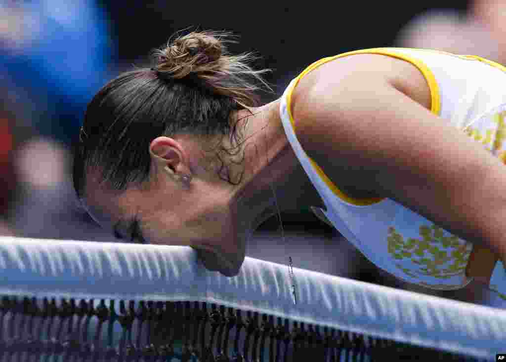 Flavia Pennetta of Italy bites the net in frustration during the fourth round match against Angelique Kerber of Germany at the Australian Open tennis championship in Melbourne, Australia.