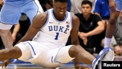 FILE - Duke's Zion Williamson sits on the floor after his shoe split open during the first half of an NCAA college basketball game against North Carolina in Durham, N.C., Feb. 20, 2019.