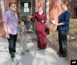 FILE - Syrian refugees Abdullah, left, Fatema, second from right, and their son, Ayham, speak with Liese Klein, development and communications manager for Integrated Refugee & Immigrant Services, outside the agency's office in New Haven, Connecticut, Sept. 2, 2016.