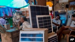 FILE - Solar panels are displayed for sale at a market in New Delhi, India, Oct. 1, 2015.