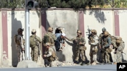 Afghan security personnel rescue a man from the Shamshad TV compound after an attack in Kabul, Nov. 7, 2017.