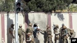 Forças afegãs socorrem um homem na Shamshad TV, Kabul, 7 de Novembro, 2017