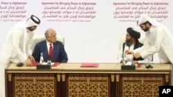 AQSh vakili Zalmay Xalilzod (chapda) va Tolibon yetakchilaridan biri Mulla Abdul G'ani Birodar tinchlik bitimini imzolamoqda, Doxa, Qatar, 2020-yil, 29-fevral